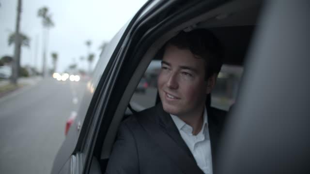 vidéos et rushes de ms young man riding in the back seat of a car - intérieur de véhicule