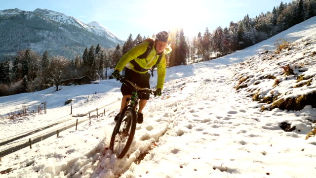 young man riding mountain bike in the snow - mountain bike stock videos & royalty-free footage