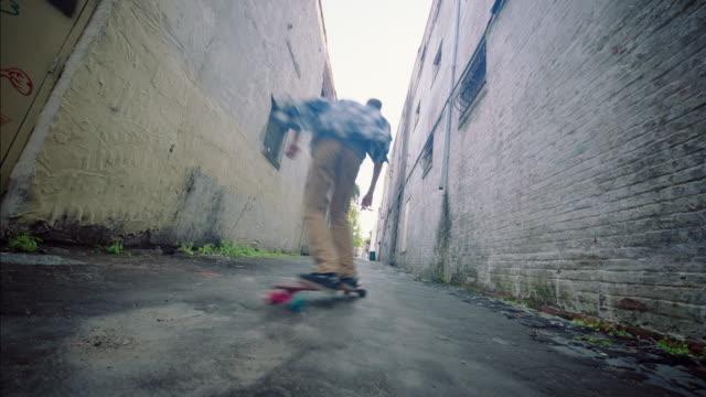 Young man riding skateboard speeds through urban alleyway