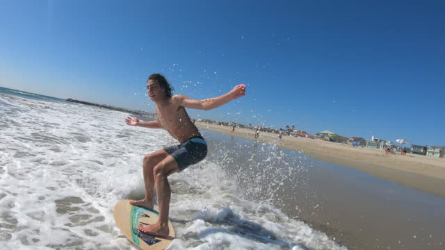 young man riding skim board on the beach into the waves - skimboarding stock videos & royalty-free footage
