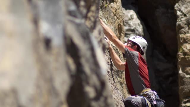 A young man rock climbing on a mountain.