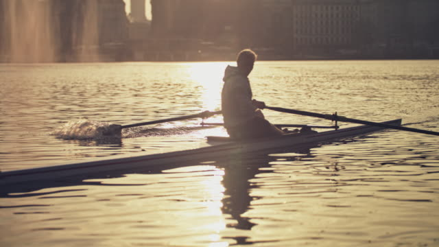 young man rowing boat in river during sunset - rowing stock videos & royalty-free footage