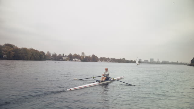 young man rowing boat in river - sculling stock videos & royalty-free footage