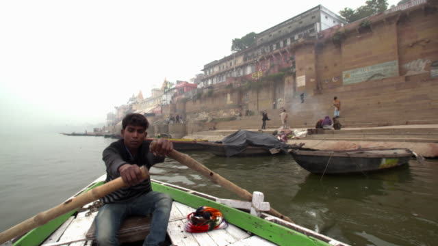 Young Man Rowing in front of Gaths in a Foggy Morning