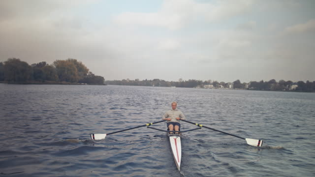 young man rowing in river - sculling video stock e b–roll