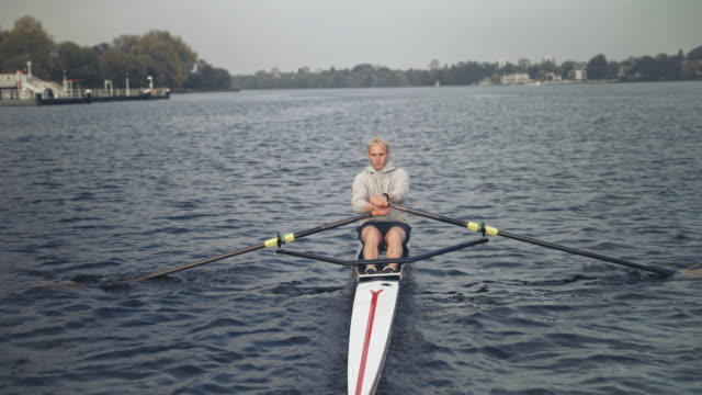young man rowing in river - sculling stock videos & royalty-free footage