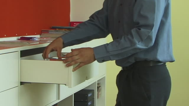 cu, young man rummaging in drawers in office - drawer stock videos & royalty-free footage