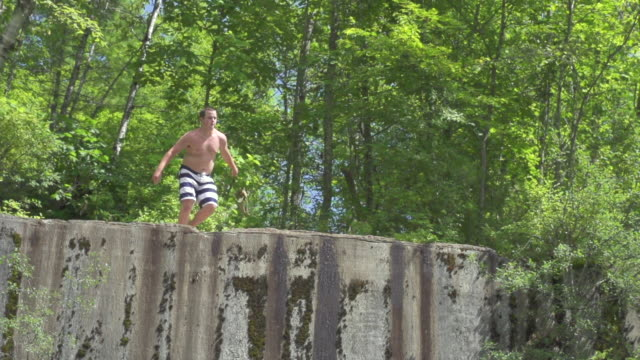 MS TD TS SLO MO Young man runing and jumping over cliff into water below / Dorset, Vermont, United States