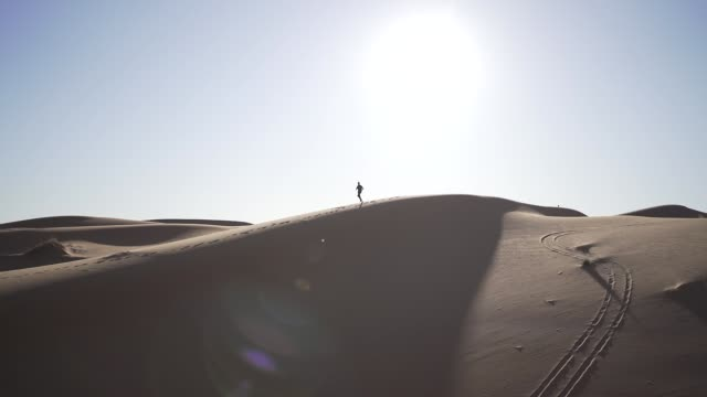 young man running across a dune in the sahara desert in morocco - 曲線点の映像素材/bロール