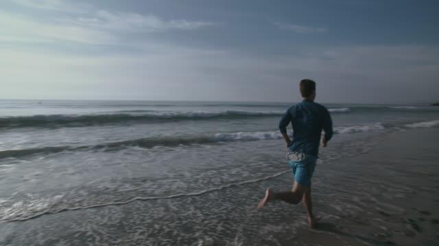 vidéos et rushes de sm ws rv young man running along the beach - cheveux courts