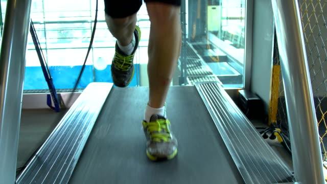 junger mann läuft und läuft auf laufband unter der kontrolle seines trainers - laufband stock-videos und b-roll-filmmaterial
