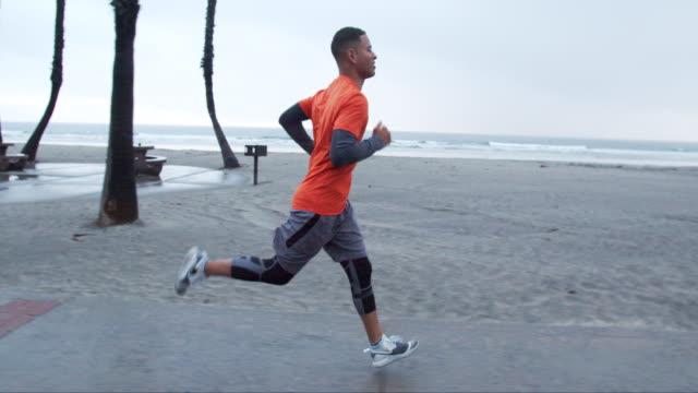 vidéos et rushes de young man running by the ocean in the rain - acier