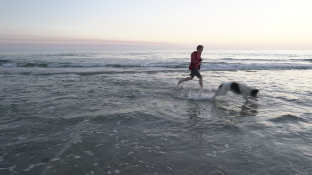 SM WS Young man running down the beach with his dog at sunset