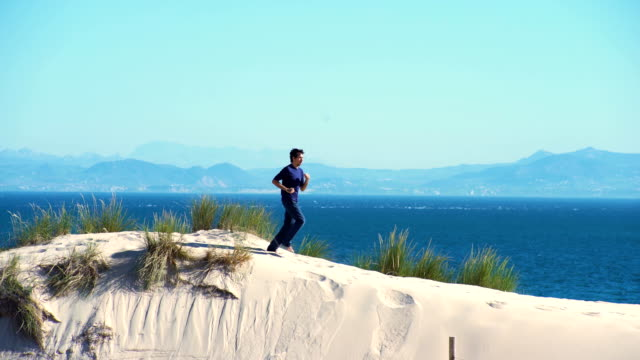 a young man running in a dune sand with ocean and africa coast behind him - only mid adult men stock videos & royalty-free footage