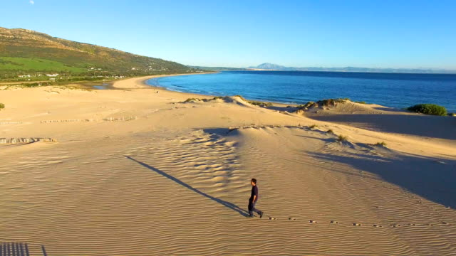 a young man running in a dune sand with ocean and africa coast behind him - cádiz stock videos and b-roll footage