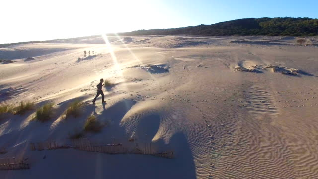 a young man running in a dune sand with ocean and africa coast behind him - one mid adult man only stock videos & royalty-free footage