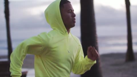 vídeos y material grabado en eventos de stock de tu young man running in the rain at dusk - correr