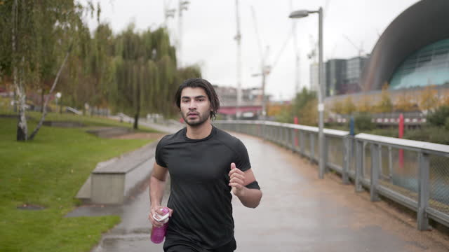 a young man running in the rain - running stock videos & royalty-free footage