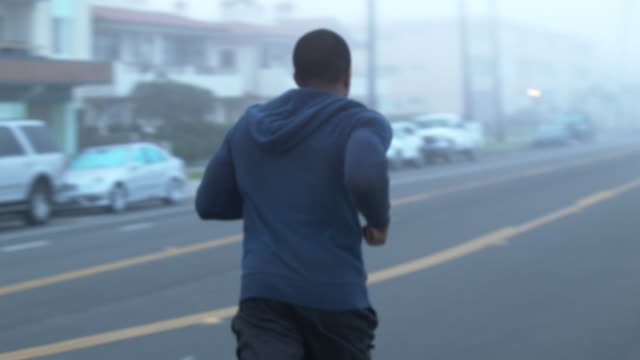 A young man running in the streets of a residential neighborhood by the beach.