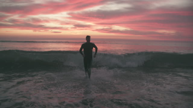ws sm young man running into the sea at sunset - kurzes haar stock-videos und b-roll-filmmaterial