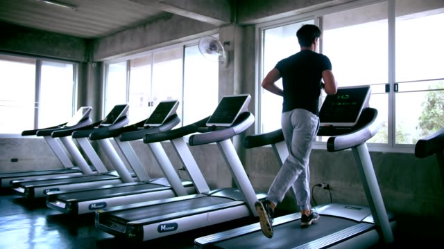 vídeos de stock, filmes e b-roll de jovem homem correndo em uma esteira - hora do dia