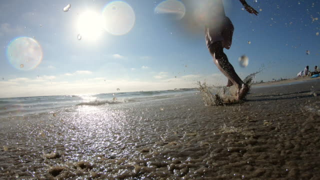 young man running on beach and jumping on skimboard - skimboard stock videos and b-roll footage