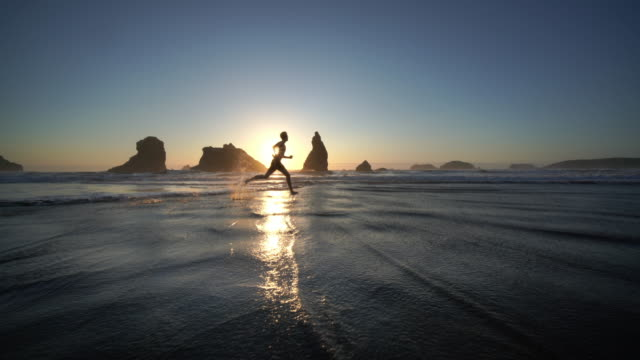 young man running on ocean beach, bandon oregon - beach stock videos & royalty-free footage