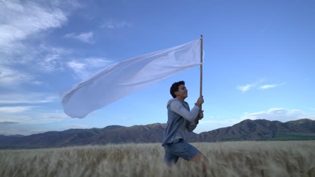 vídeos de stock, filmes e b-roll de ws sm ts young man running through a field holding a giant white flag. - só um menino adolescente