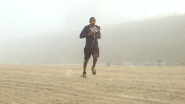 a young man running through a flock of resting seagulls on the beach. - goodsportvideo stock videos and b-roll footage