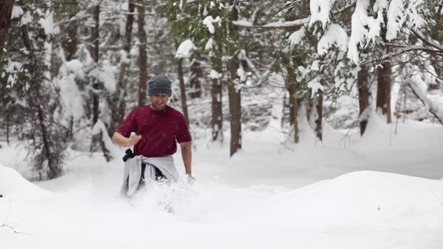 Young man running through a snow trail