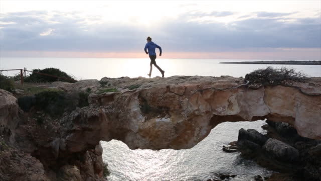 stockvideo's en b-roll-footage met young man runs along crest of rock bridge, looks off, continues - repubiek cyprus