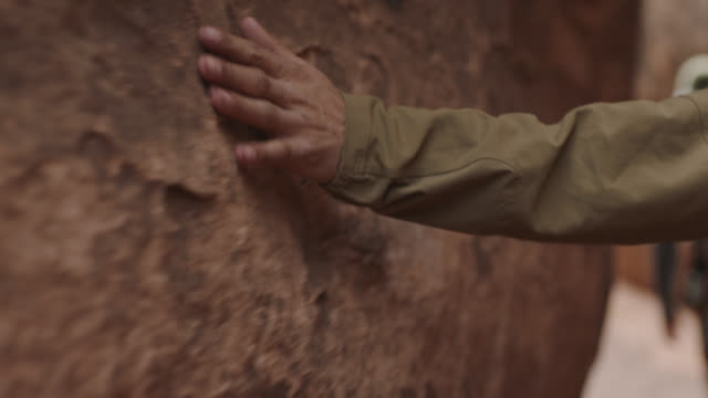 Young man runs hand along sandstone wall of slot canyon on Moab hiking trip.