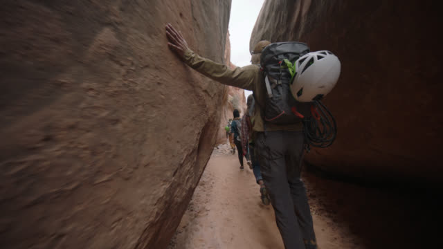 SLO MO. Young man runs hand along sandstone walls of Entrajo Canyon on hiking adventure with friends.