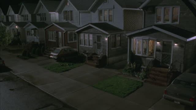 vídeos de stock, filmes e b-roll de a young man runs into a house in a suburban neighborhood at night. - distrito residencial