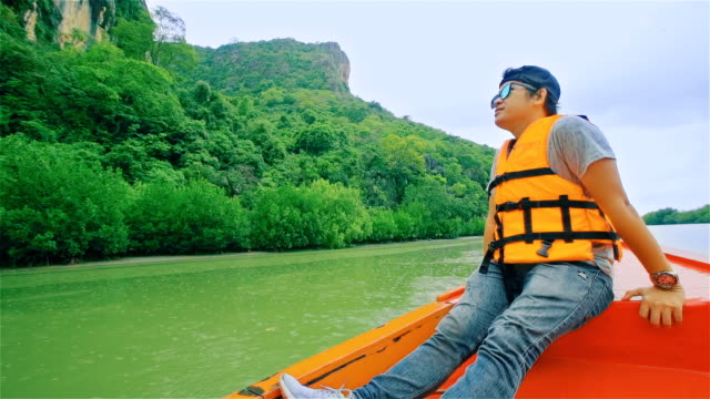 Young man sailing on a long tail thailand boat  through the mangrove forest in southern Thailand