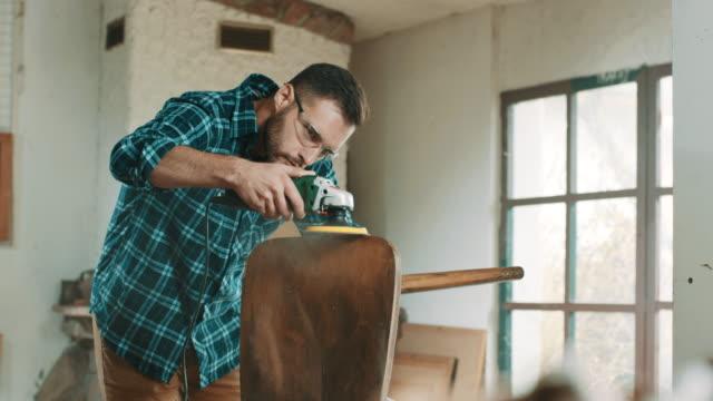 若い男が椅子を研磨 - 若い男性一人点の映像素材/bロール