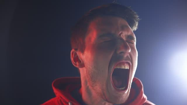 slo mo ld junger mann schreit laut - shaking stock-videos und b-roll-filmmaterial