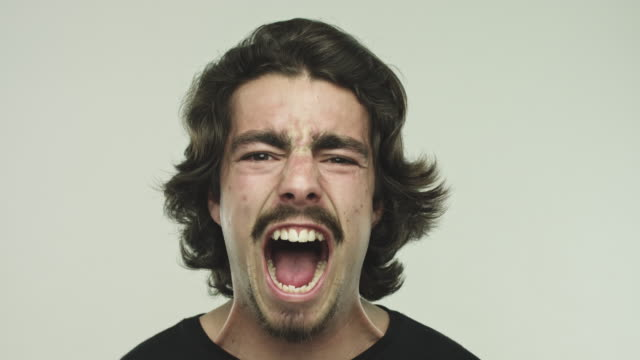 Young man screaming on gray background