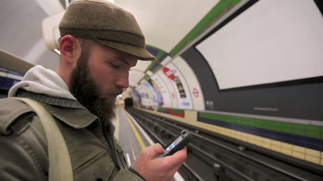 A young man looks through photos on his cell phone while waiting for the subway.