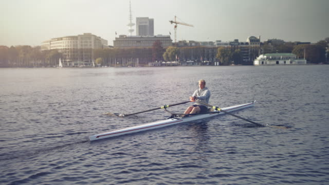 young man sculling on river during sunny day - sculling video stock e b–roll