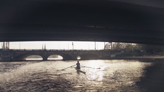 young man sculling rowboat in river on sunny day - arch bridge stock videos & royalty-free footage