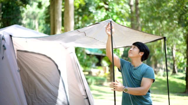 young man setting up tent in campsite. - installing stock videos & royalty-free footage