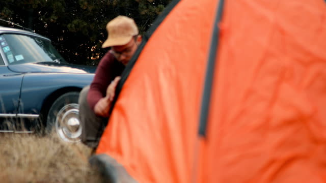 young man setting up the tent on mountain - tent stock videos & royalty-free footage