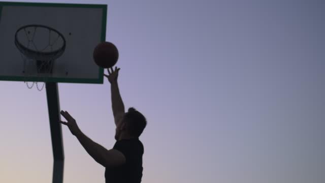 vidéos et rushes de ms jeune homme tirant des cerceaux sur le terrain extérieur de basket-ball au crépuscule - plan en travelling