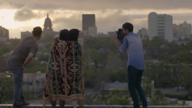 Young man shoots footage of friends with vintage film camera on rooftop overlooking downtown Austin, Texas