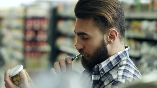 Young man shopping and vaping