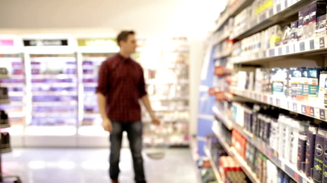 young man shopping deodorant, panning shot - decisions stock videos & royalty-free footage