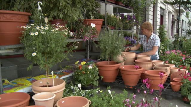 vídeos de stock e filmes b-roll de ws zi zo young man shopping for plants in front of flower shop / berlin, germany - florista
