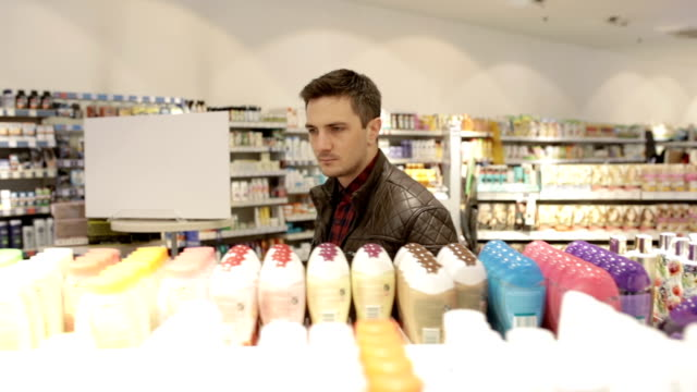 Young man shopping hygiene products, panning shot