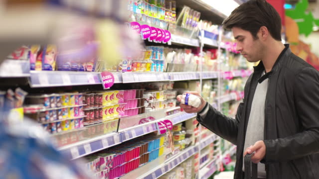 DOLLY: Young man shopping in a supermarket